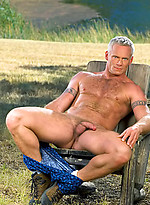 Hairy muscle man posing outdoors. Mature bodybuilder.